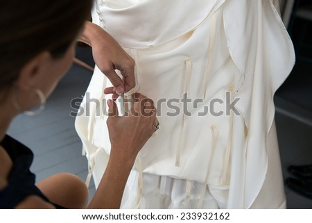 Maid of honor ties bustle on bride's wedding dress - stock photo