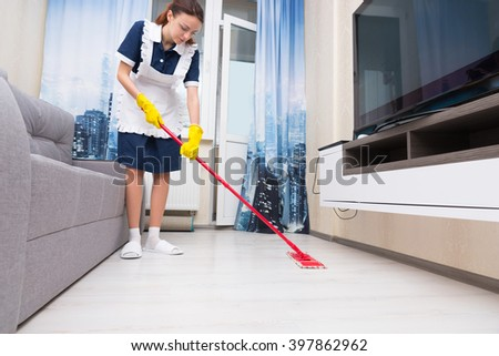 Maid or housekeeper in a neat white apron cleaning a living room floor with a colorful red mop, low angle view at floor level - stock photo