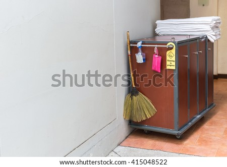 Maid's cart with a towel in hotel corridor - stock photo