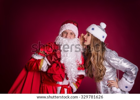 Maiden whispers something in the ear of Santa Claus - stock photo