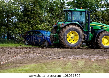 MAIDSTONE, UK - JULY 13:The Kent county show is canceled for the first time ever due to serious mud and rain problems, tractors wait to pull cars out of the mud in Maidstone, UK on the July 13, 2012