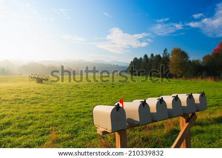 Mail boxes and an antique farm implement in a farming landscape, Stowe Vermont, USA - stock photo