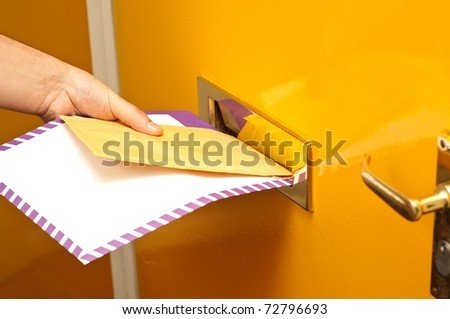 Mailman putting mail in a mailslot - stock photo