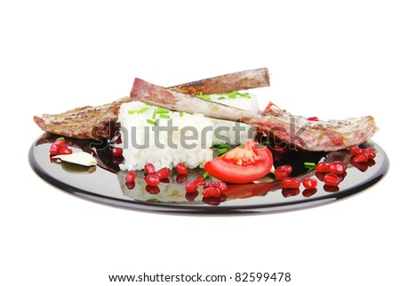 main course: grilled ribs with rice and tomatoes on black dish over white background