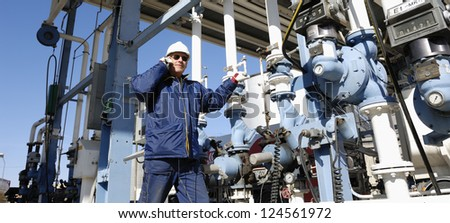 main oil and fuel station inside large oil and gas refinery, worker talking in phone - stock photo