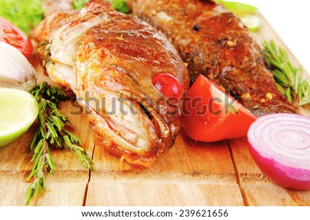 main portion of two grilled fish served on wooden plate - stock photo