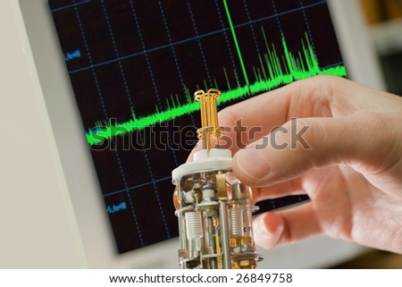 main sensor of spectrometer against spectrum on a screen - stock photo