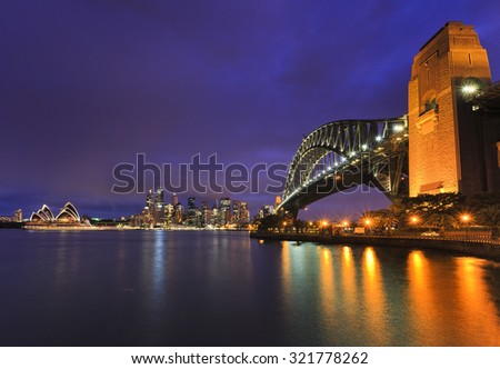 Main Sydney city richly illuminated landmarks at twilight from across harbour from Milsons point with lights reflecting in blurred waters - stock photo