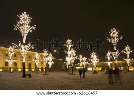 main town square covered with snow by christmas in Sibiu Transylvania Europe Romania with lights and specific decoration - stock photo