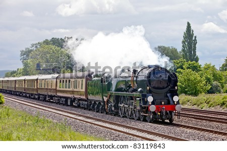 Mainline steam locomotive on a day trip to the coast with passengers aboard very high luxury carriages - stock photo