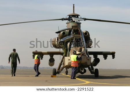 Maintenance crew helping the pilots get out of the helicopter - stock photo