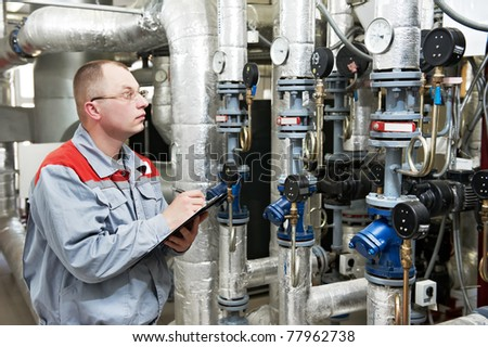 maintenance engineer checking technical data of heating system equipment in a boiler house - stock photo