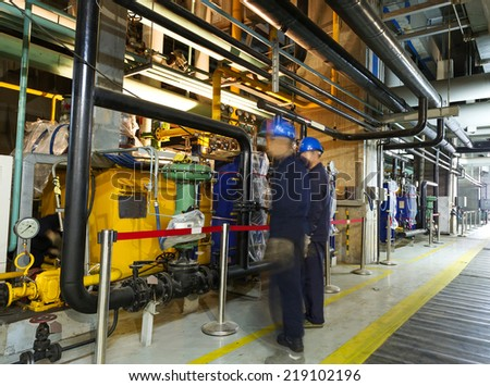 maintenance engineers checking technical data of heating system equipment in a boiler room - stock photo