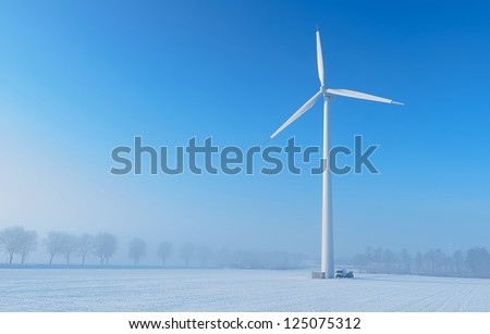 Maintenance on a giant wind turbine in a cold and foggy winter landscape