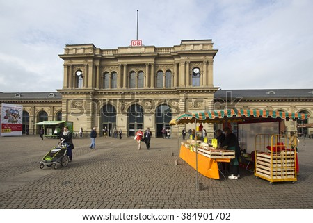Mainz, Germany - April 29, 2014: People leaving the Mainz railway station, walking past a fruit stall in Mainz, Germany on April 29, 2014