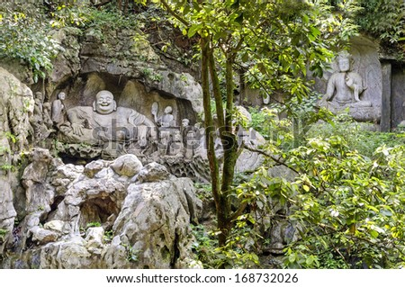 Maitreya and disciples, in Budai form, as depicted at the Feilai Feng grottos near Lingyin Temple in Hangzhou, China. Budai is a Chinese folkloric deity. - stock photo