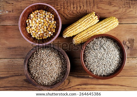 Maize, wheat, rye, meal and ceramic bowls on wooden table - stock photo