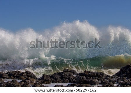 Majestic backwash from the  Indian Ocean waves breaking on basalt rocks at  Ocean Beach Bunbury Western Australia on a sunny morning in mid-winter  sends salty spray high into the air.