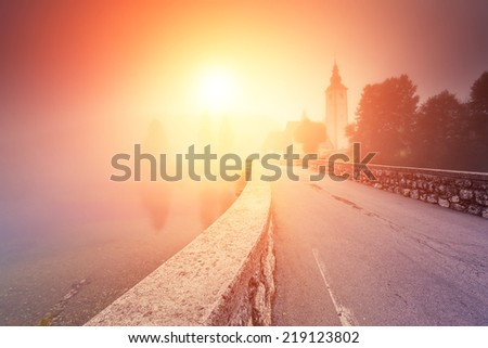 Majestic colorful foggy morning scene in the Triglav national park, located in the Bohinj Valley of the Julian Alps. Dramatic view of the church St. John the Baptist. Slovenia, Europe. Beauty world.. - stock photo