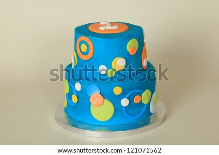 Majestic double tier round butter iced birthday celebration cake with blue frosting and yellow and orange polka dots - stock photo