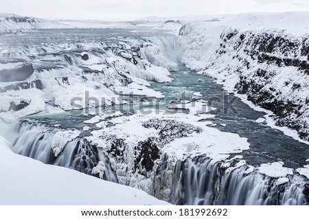 Majestic Gullfoss waterfalls form a half frozen triangle as the Hvita River falls into a wintry gorge in Western Iceland - stock photo