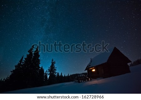 Majestic Milky Way over the winter mountains landscape. Night scene. Wooden house with light in window. Kukul ridge, Carpathians, Ukraine, Europe. - stock photo