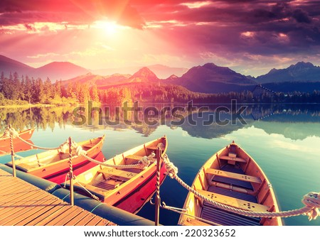 Majestic mountain lake in National Park High Tatra. Dramatic unusual scene. Sky glowing by sunlight. Strbske pleso, Slovakia, Europe. Beauty world. Retro style filter. Instagram toning effect. - stock photo