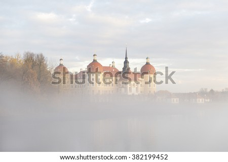 Majestic old German castle in an autumn foggy forest near calm peaceful lake.  - stock photo