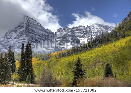 Majestic Snow Covered Mountain with Yellow Aspens and Pine Trees - stock photo