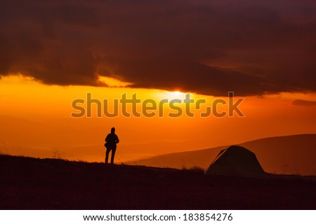 Majestic sunrise in the mountains landscape. Lonely tent on a mountain top and the silhouette of the girl. Overcast sky. Carpathian, Ukraine, Europe. Beauty world.