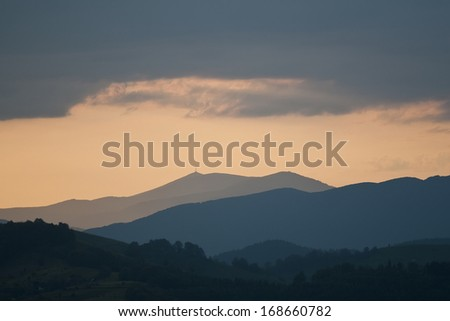 Majestic sunset in the mountains landscape. Overcast sky before storm.
