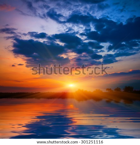Majestic sunset over lake water - stock photo