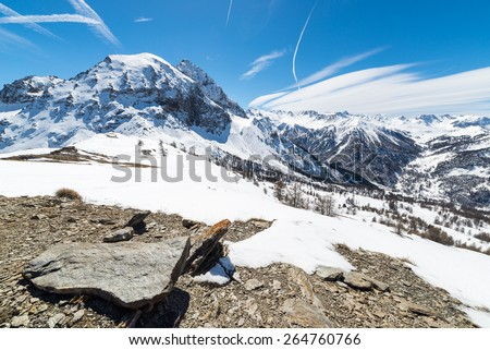 "Majestic wide angle view of snowcapped high mountain peaks in the italian alpine arc, in a bright sunny day of spring, near ""Via Lattea"" ski resort, Torino, Italy. Boulders in the foreground. - stock photo"