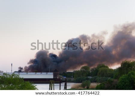 Major fire in an industrial area in Hamburg, Germany, with a large cloud of smoke. - stock photo