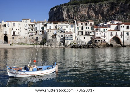 Major tourist attraction an old fishing village. The charm of a rowboat, old buildings and mountain side captured at Cefalu Beach. Located at the town of Cefalu, Sicily, Italy - stock photo