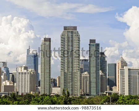 Makati skyline shot against blue sky and clouds - stock photo