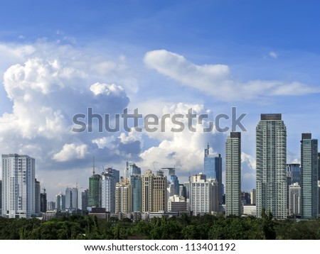 Makati skyline shot against blue sky and swirling clouds