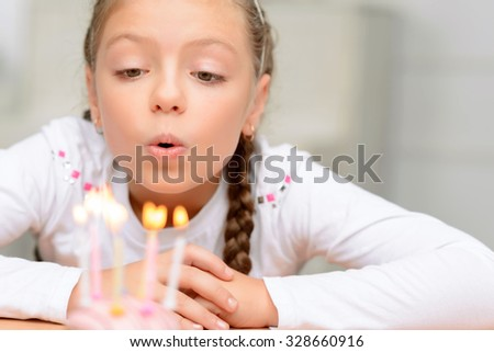 Make a wish. Cheerful delighted little girl sitting at the table and blowing the candles while having birthday party - stock photo