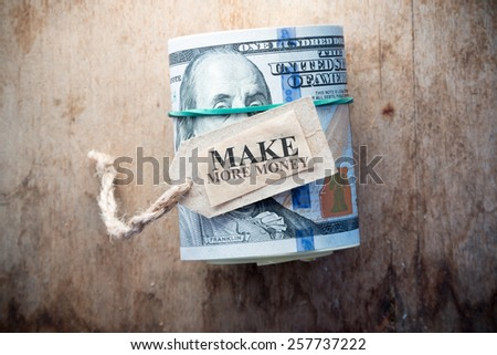 Make More Money,  inscription, on the  background wooden table and one hundred dollar bills. - stock photo