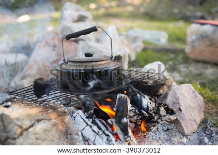 Make tea over an open fire in a hike in the woods. - stock photo