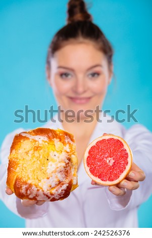 Make the right dietary choice concept. Nutritionist comparing diets options, holding cake sweet food and grapefruit on blue - stock photo
