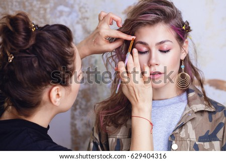 Make-up artist and model at work, focus on model's face, close up