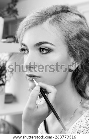 Make-up artist applying lipstick on model's lips, close up. Black and white - stock photo
