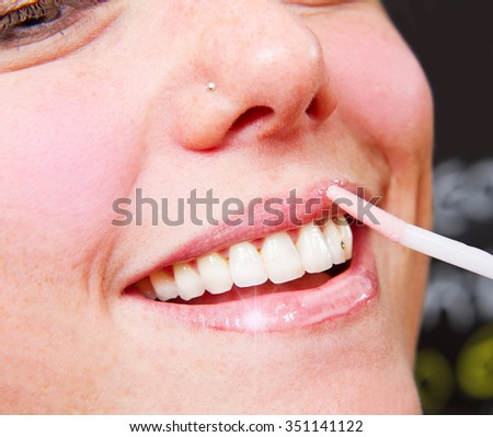 Make-up artist applying lipstick with a brush - stock photo