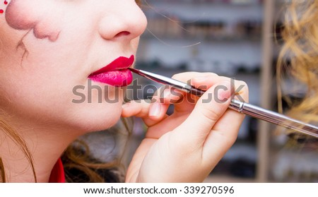 Make-up artist applying lipstick with a brush on model's lips, close-up - stock photo