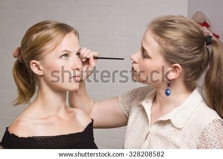 Make-up artist applying liquid eyeliner with brush, close up - stock photo