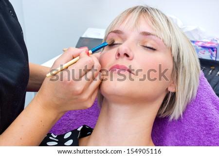 make up artist applying make up on model with brush - stock photo
