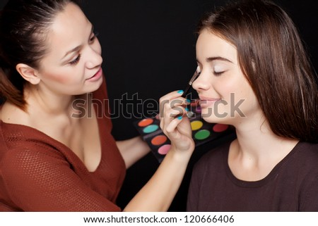 Make up artist applying make up to a fashion model - stock photo