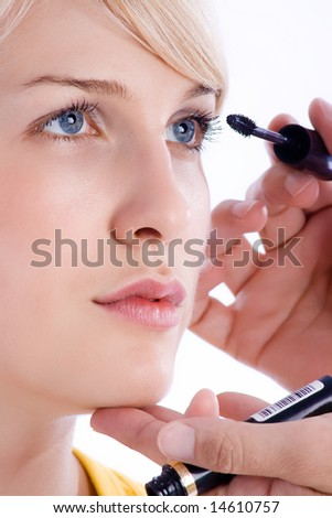 make up artist applying mascara on female model - stock photo