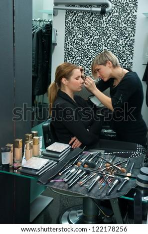 make up artist applying mascara on model eyelashes - stock photo